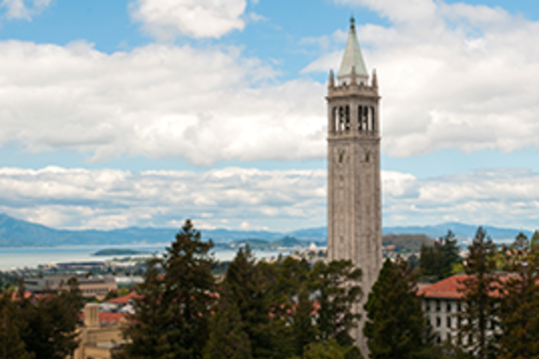 UC Berkeley's campanile against a blue sky with white clouds