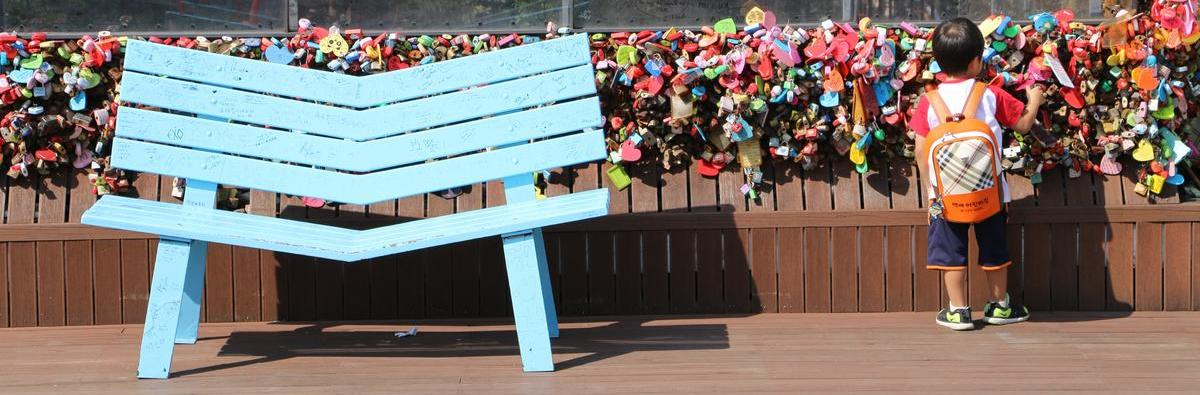 Little boy next to blue bench at N Seoul Tower