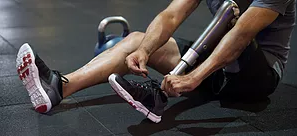 Man ties his shoe on a prosthetic leg.